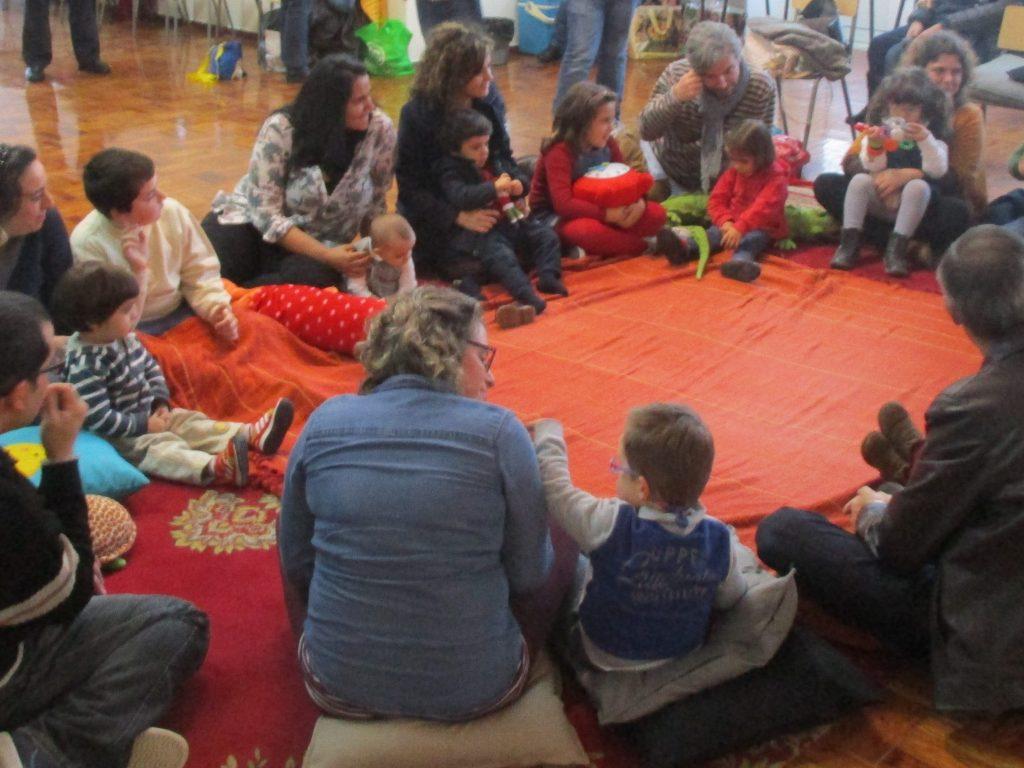 Vários familiares e crianças sentados em roda numa atividade conjunta
